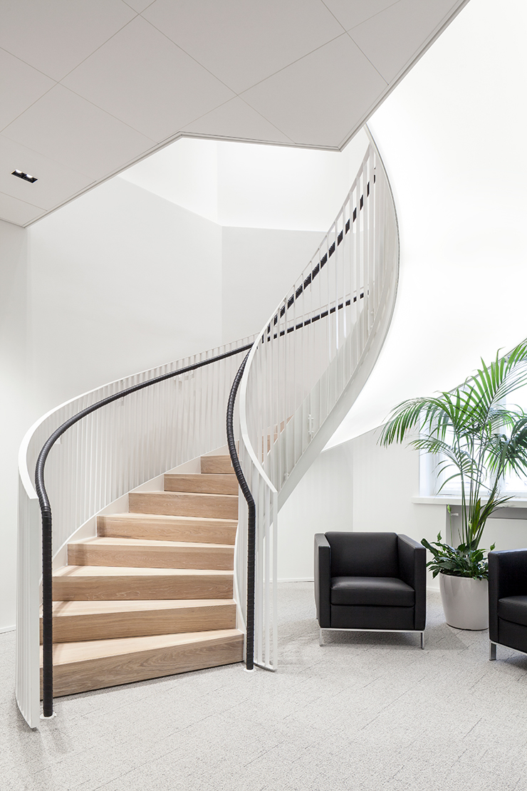 The black leather handrail of the interior staircase matches the black leather furniture the stairs are lit from below the steps